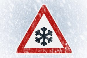 Winter driving - ice covered windshield with warning sign